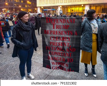 Daley Plaza, Chicago-January 20, 2017. Post-Inauguration Trump Protest. Two female opposers of Donald Trump display a handwoven banner that expresses Donald Trump is a danger to women.