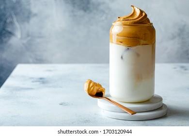 Dalgona Kaffee. Iccied Flauschig cremig Peitsche Trenddrink mit Kaffeeschaum und Milch. Trendgetränk während der Covid-19 City-Absperrung und Selbstisolierung, bleiben Sie zu Hause Konzept.