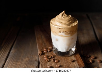 Dalgona coffee - the Korean coffee drink on wooden background. Cappucino turned on its head, with the frothy coffee on top and the milk underneath.