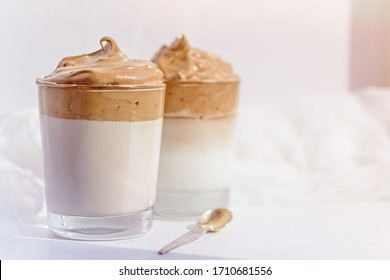 dalgona coffee with whipped foam in glasses on white background in morning light, korean coffee concept