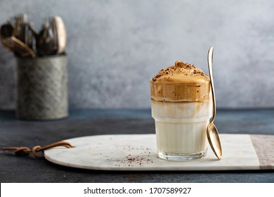 Dalgona coffee or whipped instant coffee. New popular food and drink trend. Light background, one glass with copy space