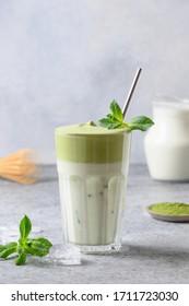 Dalgona Matcha latte tea with milk and whipped tea garnish mint. Close up. Vertical format.