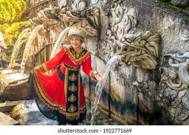 Dali China , 6 October 2020 : Woman in Bai minority traditional ethnic dress in front of the five dragons pool fountain in the Butterfly spring park in Dali Yunnan China