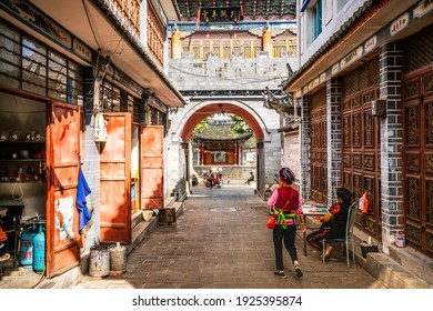 Dali China , 6 October 2020 : Zhoucheng ancient village alley view with Bai minority woman in traditional dress in Zhoucheng Dali Yunnan China