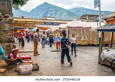 Dali China , 6 October 2020 : Zhoucheng village market place view with Bai minority people in traditional dress and Cangshan mountain in background in Dali Yunnan China