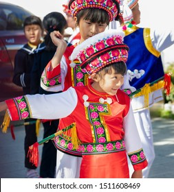 Dali, China - December 27, 2018: Two girls of Bai people dressed in traditional Bai clothings dancing in Dali, Yunan, China.