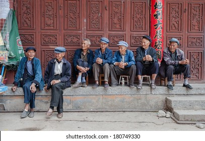 DALI, CHINA - JULY 8: Elderly people sit in front of a social welfare home on July 8, 2013 in Dali, China.In China there is a shortage of elderly care with thousands of applicants on the waiting list.