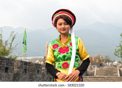 DALI, CHINA - MARCH 20, 2014: A woman dressed in ancient Bai nationality clothing, smiling and welcome the travelers from all over the world. Located in Dali Ancient City, Yunnan Province, China.