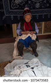 Dali, China - March 23, 2018: Bai woman hand dyeing fabrics with indico blue