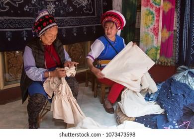 Dali, China - March 23, 2018: Bai women hand dyeing fabrics with indico blue
