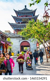 Dali, China - March 24, 2014: People are walking in Dali Ancient City (Dali Old Town). The text on the gate translate into English is Wuhua Tower. Located in Dali, Yunnan, China.