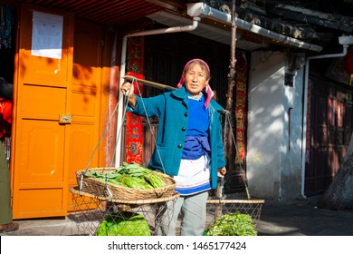 Dali, China - March 24, 2014: Farmers carrying vegetables in Dali Ancient City (Dali Old Town). Located in Dali, Yunnan, China.
