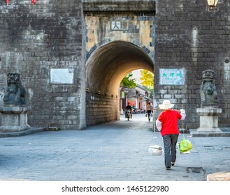Dali, China - March 25, 2014: People are walking in Dali Ancient City (Dali Old Town). The text on the gate translate into English is Dali. Located in Yunnan, China.