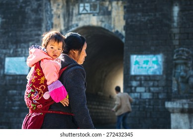 Dali, China - March 25, 2014: People walking in the old town of Dali in the morning. In the distance is North Gate of Dali Old Town. Located in Yunnan Province, China.