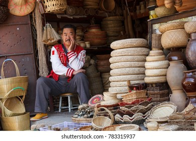 Dali, Yunnan, China- 02.01.2017: Man sitting in his shop selling wicker products