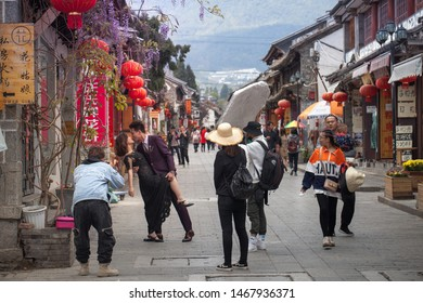 Dali, Yunnan province / China - May 2019 : City of photographers and weddings photoshoots. This couple's wedding photo shoot on the streets of Dali is positively modest by modern Chinese standards.