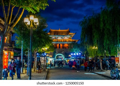 """Dali, Yunnan province / China - Oct 2018: Ancient Chinese architecture turret building in Old Town. Nigth market street full of tourists. The translation is """"Dali Old Town and Wuhua building""""."""