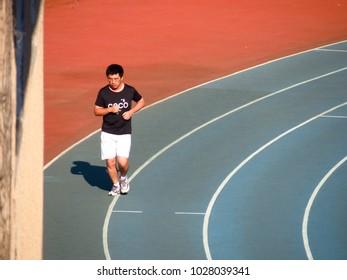 Dalian, China - JUL 09, 2015: A man is running in sport field at Dalian, China