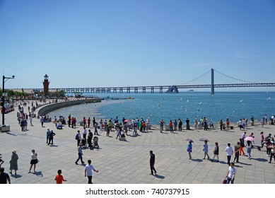 DALIAN, CHINA - June 11, 2017: Tourists walking around at Xinghai Square, Dalian, the largest city square in the world, the Xinghai Bay Bridge could be seen.