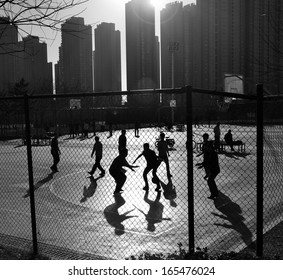 DALIAN, CHINA - NOVEMBER 30: Unidentified group of youths playing basketball in a urban playground in Dalian Development Area, November 30, 2013.