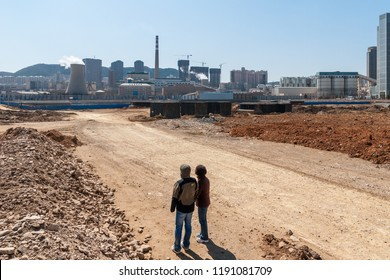 Dalian, Liaoning, China - March 25 2012: Two Chinese people looking from Zhuccui Street to the Dalian Thermal Power Plant