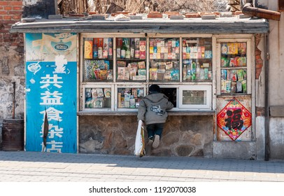 Dalian, Liaoning, China - March 25 2012: Little boy, buying candies at a kiosk in middle of a typical Dalian housing block. And yes, the kiosk is next to a school