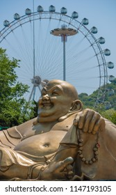 Dalian, Liaoning, China - May 21 2009: Front view of the giant Buddha statue in Dalian Labour Park. In the background the Ferris Wheel.
