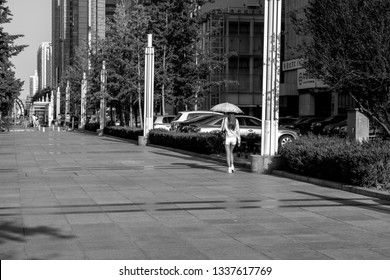 Dalian,China - August 2016 Woman walking down a unusually quite sidewalk in china, in black and white.