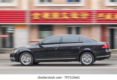 DALIAN-NOV. 25, 2012. Accelerating black VW Passat. VW will invest over $12 billion with its partners to develop a range of new-energy low-emission cars in China, the biggest car market in the world.