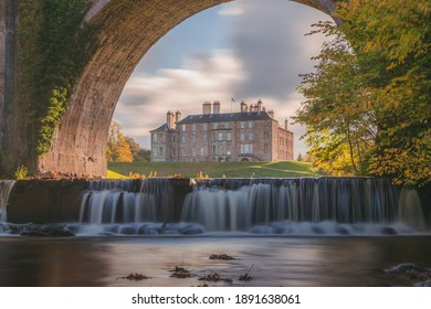 Dalkeith Country Park with waterfall and arch framing manor house on a sunny autumn afternoon makes for an ideal day trip from Edinburgh in Scotland. - Shutterstock ID 1891638061