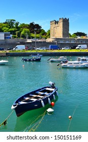 DALKEY, IRELAND – CIRCA JUNE: A small blue wooden boat moored at Bulloch Harbour circa June, 2013 in Dalkey, Ireland. In the background is Bulloch Castle which was built in 1150.