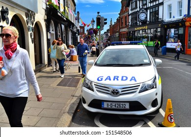 DALKEY, IRELAND - JUNE 18: Unidentified people walk past a police car during the visit of U.S. First Lady, Michelle Obama, on June 18, 2013 in Dalkey, Ireland