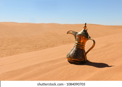 A Dallah traiditonal pot on a red sand desert