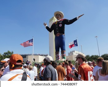 DALLAS, TEXAS—OCTOBER 2017:  People mill around the Big Tex statue who speaks and waves his hands to welcome visitors to the State Fair of Texas carnival grounds in Dallas.