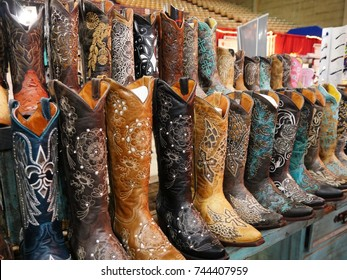 DALLAS, TEXAS—OCTOBER 2017:  A row of colorful artistically designed knee-high boots displayed inside one of the buildings at the State Fair of Texas carnival grounds in Dallas.