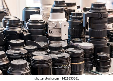 Dallas, Oregon - June 7, 2019: Variety of used DSLR camera lenses stacked on a table.