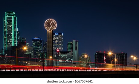 Dallas skyline by night with traffic trails on Tom Landry freeway