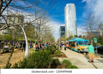 DALLAS, TEXAS - CIRCA MARCH 2018: People walk around Kyde Warren Park in downtown Dallas and purchase food from food trucks.