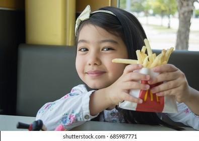 DALLAS, TEXAS - July 23, 2017:  Little consumer eating happy meal at Mcdonald's  Dallas, Texas
