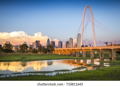 The Dallas, Texas skyline reflects of a pond under the Margaret Hunt Hill Bridge.