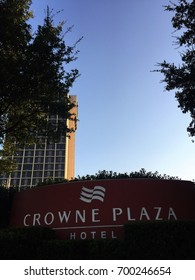 DALLAS, TEXAS, USA - AUGUST 19, 2017: A picture of Crowne Plaza Hotel Dallas logo taken in front of the hotel entrance with green trees and the hotel building in the background.