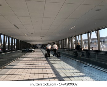 DALLAS, TEXAS, USA - AUGUST 5, 2019: Two male crews in uniform carry baggages and walk together on the walkway in Dallas Fort Worth International Airport. It is a sunny day with shadows on the floor.