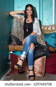 Dallas, Texas / USA - July 26, 2016: Attractive Hispanic Woman Wearing a Print Cardigan and Distressed Jeans Sitting in a Boutique Shop Dressing Room