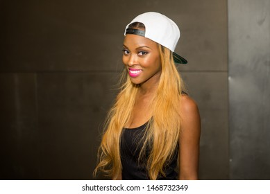 Dallas, Texas / USA - July 27, 2014: Portrait of an Attractive African American Woman Smiling Wearing a Baseball Hat Backwards