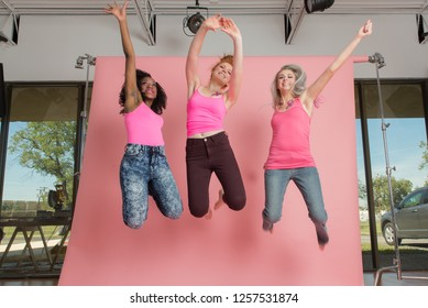 Dallas, Texas / USA - October 17, 2014: Portrait of a Three Young Pretty Women Jumping in a Photography Studio in Pink Tank Tops with  Breast Cancer Awareness Stickers on Their Chest