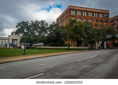 Dallas, TX - 9/22/18: Tourists visit the site of President Kennedy's assasination, marked by a white X in the street