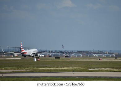 Dallas, TX - May 14, 2020: An American Airlines 737 Lands at Dallas/Ft. Worth International Airport with Aircraft Grounded by the Coronavirus Pandemic in the Background