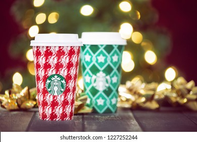 Dallas, TX - November 10, 2018: Starbucks popular holiday beverage, served in the new 2018 designed holiday cups. Festive holiday Christmas tree lights background.