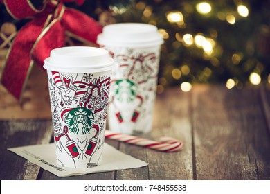 Dallas, TX - November 4, 2017: Starbucks popular holiday beverage, served in the new 2017 designed holiday cups. Displayed with candy cane on wooden rustic table. Christmas tree lights background.