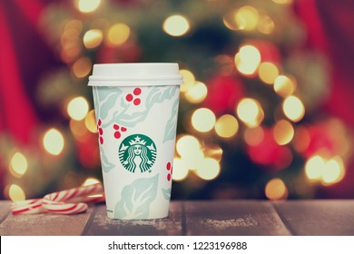 Dallas, TX - November 5, 2018: Starbucks popular holiday beverage, served in the new 2018 designed holiday cup. Displayed on rustic table with candy canes. Festive Christmas lights background.
